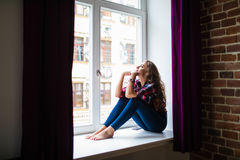 Sad young adult woman sitting on a window royalty free stock photo