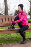 Sad young athlete woman sitting on a bench Royalty Free Stock Image