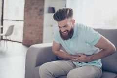 Sad young bearded man is suffering from stomach pain, ache is ve. Ry hard. He is alone at home, sitting on couch Stock Photo