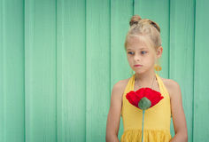 Sad young blond girl holding a red flower Stock Image
