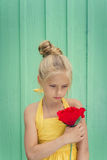 Sad young blond girl holding a red flower Stock Photo
