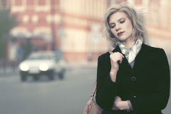 Sad young blond woman in black coat walking in city street Royalty Free Stock Photography