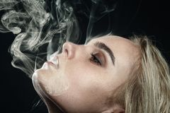 Blond girl smoking. Sad young blond woman with closed eyes on dark background smoking Stock Photography