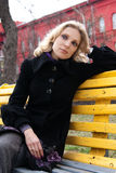 Sad young blonde sitting on a bench in the park Stock Photo