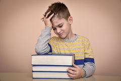 Sad young boy and books Royalty Free Stock Images