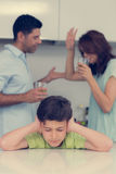 Sad young boy covering ears while parents quarreling Royalty Free Stock Photos