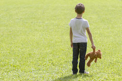 Sad young boy is holding a brown teddy bear and standing on the meadow. Back view. Copy space. Sadness, fear Stock Photography