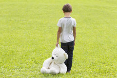 Sad young boy is holding a teddy bear and standing on the meadow. Child looking down. Back view. Sadness, fear. Sad young boy is holding a teddy bear and Royalty Free Stock Photo