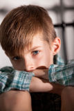 Sad Young Boy with Knees Up Looking at the Camera. Close up Blond Young Boy with Knees Up and Folded Arms  Looking Straight at the Camera with Sad Facial Royalty Free Stock Photos