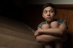 Sad young boy. Sitting on some stairs stock images