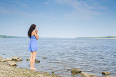 Sad young brunette woman in blue summer dress standing on the river bank stock image