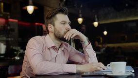Sad young business man in a bar. Sad young business man sitting at the table with laptop and papers in a restaurant stock footage