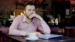 Sad young business man in a bar. Sad young business man sitting at the table with laptop and papers in a restaurant stock video