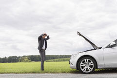 Sad young businessman standing with hands on head near broken car at countryside Royalty Free Stock Images