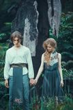 Young couple of elves outdoor agaist dying burned-down tree. Sad young couple of elves in magical forest agaistdying burned-down tree outdoor on nature. Fairy royalty free stock images