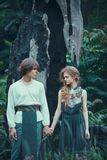 Young couple of elves outdoor agaist dying burned-down tree. Sad young couple of elves in magical forest agaistdying burned-down tree outdoor on nature. Fairy stock image