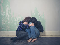 Sad young couple on floor Royalty Free Stock Photography
