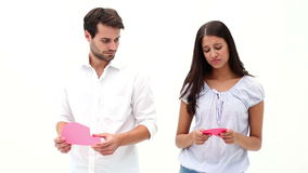 Sad young couple holding two halves of broken heart. On white background stock footage