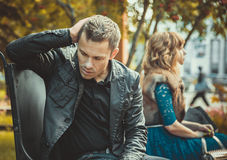 Sad young couple. Sitting on the bench after a quarrel royalty free stock photo