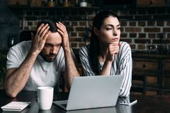Sad young couple sitting on kitchen with laptop. And calculator royalty free stock images