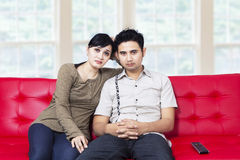 Sad young couple watching television Stock Photography