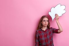 A sad girl, holds a paper image of thoughts or ideas above head and gaze furtively into the distance. A sad young European girl, a brunette, holds a large paper Royalty Free Stock Photos