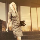 Sad young fashion business woman with handbag at office building royalty free stock photography