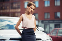 Sad young fashion business woman beside her car Stock Photos