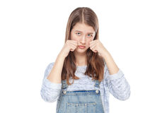 Sad young fashion girl in jeans overalls isolated Royalty Free Stock Image