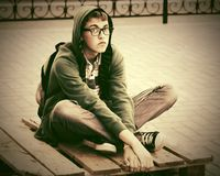Sad young fashion hipster man sitting on sidewalk in city street. Sad young fashion hipster man in a hoodie sitting on sidewalk in city street Royalty Free Stock Photography
