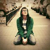 Sad young fashion hipster man sitting on city sidewalk. Sad young fashion hipster man sitting on sidewalk in city street Stock Photos