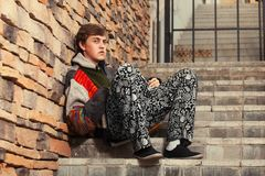 Sad young fashion hipster man sitting on the steps Stock Photography