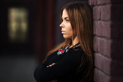 Sad young fashion woman in black dress at the brick wall Stock Photo