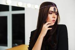 Sad young fashion woman in black jacket next to makeup mirror Royalty Free Stock Image