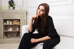 Sad young fashion woman in black jacket sitting on sofa Stock Image