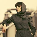 Sad young fashion woman in classic coat and headscarf Royalty Free Stock Photography