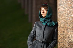 Sad young fashion woman in classic coat at the wall Royalty Free Stock Photography