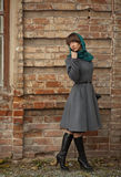 Sad young fashion woman in coat looking back near brick wall Royalty Free Stock Photography