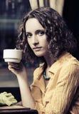 Sad young fashion woman drinking tea at restaurant stock photo