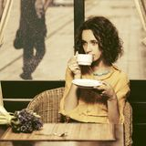Sad young fashion woman drinking tea at restaurant stock image