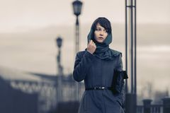 Sad young fashion woman in grey classic coat with handbag stock photography