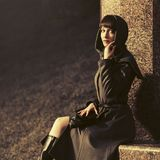 Sad young fashion woman in grey classic coat sitting on bench. At the wall in night stock photo