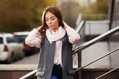 Sad young fashion woman in grey coat on city street Stock Photos