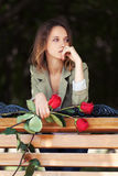 Sad young fashion woman with red roses Royalty Free Stock Images