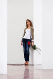 Sad young fashion woman with red roses standing at wall Royalty Free Stock Photography