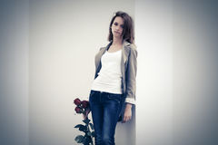 Sad young fashion woman with red roses standing at the wall Royalty Free Stock Images