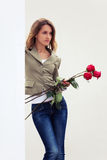 Sad young fashion woman with red roses at the wall Stock Image