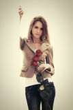 Sad young fashion woman with red roses at the wall Royalty Free Stock Images