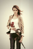 Sad young fashion woman with red roses at the wall Royalty Free Stock Photography