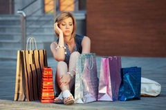 Sad young fashion woman with shopping bags sitting on sidewalk Stock Photography